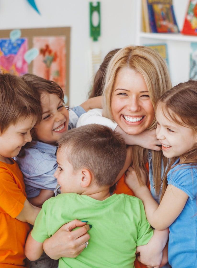 Sechs Kinder umarmen Frau